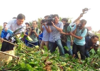 Ảnh truyền thông quốc doanh chen chân ghi hình bí thư Đinh La Thăng dọn rác. Ảnh: internet