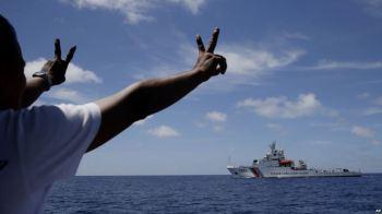 Thuyền viên Philippines ra dấu với tàu Tuần duyên Trung Quốc khi họ chặn chiếc tàu này tiến vào Bãi Cỏ Mây ở Biển Đông, 29/3/2014. Ảnh: AP