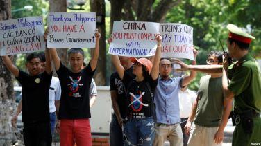 Cảnh sát cố gắng ngăn cản người biểu tình chống Trung Quốc trong một cuộc biểu tình trước đại sứ quán Philippines ở Hà Nội, ngày 17/7/2016. Ảnh: Reuters.