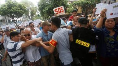 Công an cố ngăn chặn đoàn biểu tình, những người tuyên bố đòi nước sạch cho miền trung sau vụ cá chết mấy tuần trước đó, tại Hà Nội, Việt Nam – ngày 1 tháng Năm, 2016. © 2016 Reuters