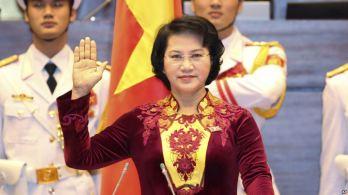 Trong lần tuyên thệ thứ nhất bà Ngân mặc áo dài đỏ lòe loẹt, cổ thêu hoa văn vàng chóe, mà không ai hiểu nổi là hình họa theo mô-típ gì. Ảnh: AP
