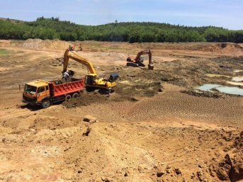 Xe vận tải chở bùn được khai thác một cách lén lút tại lòng hồ Hố Dọc để đem tới đắp nền cho cao tốc. (Hình: Lao Ðộng)