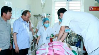 Thủ tướng Nguyễn Xuân Phúc thăm nạn nhân tại bệnh viện. Ảnh: EPA
