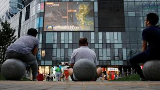 Người dân xem chương trình tin tức về Biển Đông bên ngoài một trung tâm mua sắm ở Bắc Kinh, Trung Quốc, ngày 16/07/2016. Ảnh: REUTERS/Thomas Peter