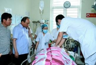 Thủ tướng Việt Nam Nguyễn Xuân Phúc (thứ hai từ trái) bên nạn nhân Phạm Duy Cường tại bệnh viện Yên Bái sáng 18/8/2016.