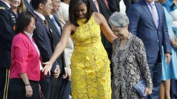 Bà Ho Chung (phải), tay cầm cái ví trị giá $11. Người mặc đầm vàng là Đệ nhất Phu nhân Michelle Obama