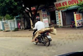 Do không có tiền thuê xe ô tô nên gia đình chị P đã nhờ người quen sử dụng xe máy chở thi thể về mai táng. Ảnh: Tùng Hải.