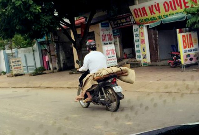 Do không có tiền thuê xe ô tô nên gia đình chị P đã nhờ người quen sử dụng xe máy chở thi thể về mai táng. Ảnh: Tùng Hải/ DV