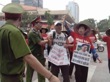 Cấn Thị Thêu phản đối công an sử dụng bạo lực. Bà mang trên tay bức hình con trai là Trịnh Bá Tư bị côn đồ thân chính quyền tấn công vào tháng Sáu năm 2015. © private.