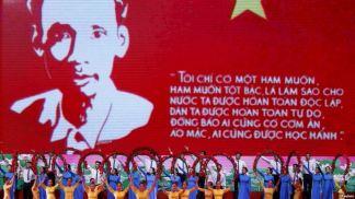 Nghệ sĩ biểu diễn trước một màn ảnh khổng lồ chiếu hình ảnh và danh ngôn của lãnh tụ Hồ Chí Minh, ở Hà Nội, 17/5/2015. Ảnh: Reuters.