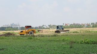 Ruộng đất của dân chưa đền bù xong nhưng các phương tiện thi công của chủ dự án vẫn ngang nhiên tiến hành san lấp. Ảnh: Lê Anh Hùng