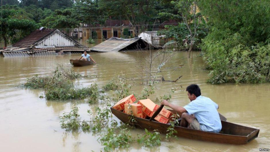 Một người đàn ông chèo thuyền vận chuyển hàng cứu trợ giúp các nạn nhân lũ lụt ở huyện Hương Khê, Hà Tĩnh. (Ảnh tư liệu). Nguồn: Reuters.