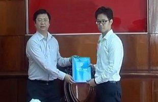 Ông Vũ Minh Hoàng (phải) nhận quyết định bổ nhiệm làm phó giám đốc Trung Tâm Xúc Tiến Đầu Tư - Thương Mại và Hội Chợ Triển Lãm của Cần Thơ rồi trở qua Nhật học tiếp. (Hình: Đài PTTH Cần Thơ)