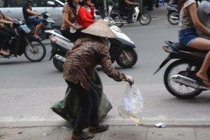 """Một người nghèo lượm rác kiếm sống trên đường phố Hà Nội. Mức độ nghiêm trọng của các thảm trạng xã hội càng ngày càng lớn vì chính quyền Việt Nam vẫn loay hoay chưa biết làm thế nào để xây dựng """"kinh tế thị trường theo định hướng xã hội chủ nghĩa."""" (Hình: Getty Images)"""