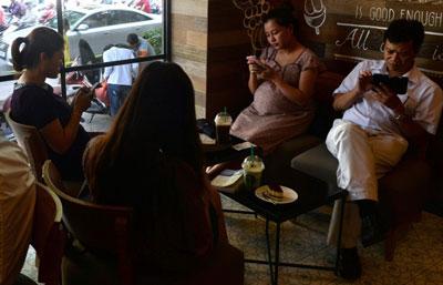 Người dân sử dụng điện thoại cầm tay, iPad lướt web trong một quán cà phê ở Hà Nội ngày 23 tháng bảy năm 2014. AFP photo