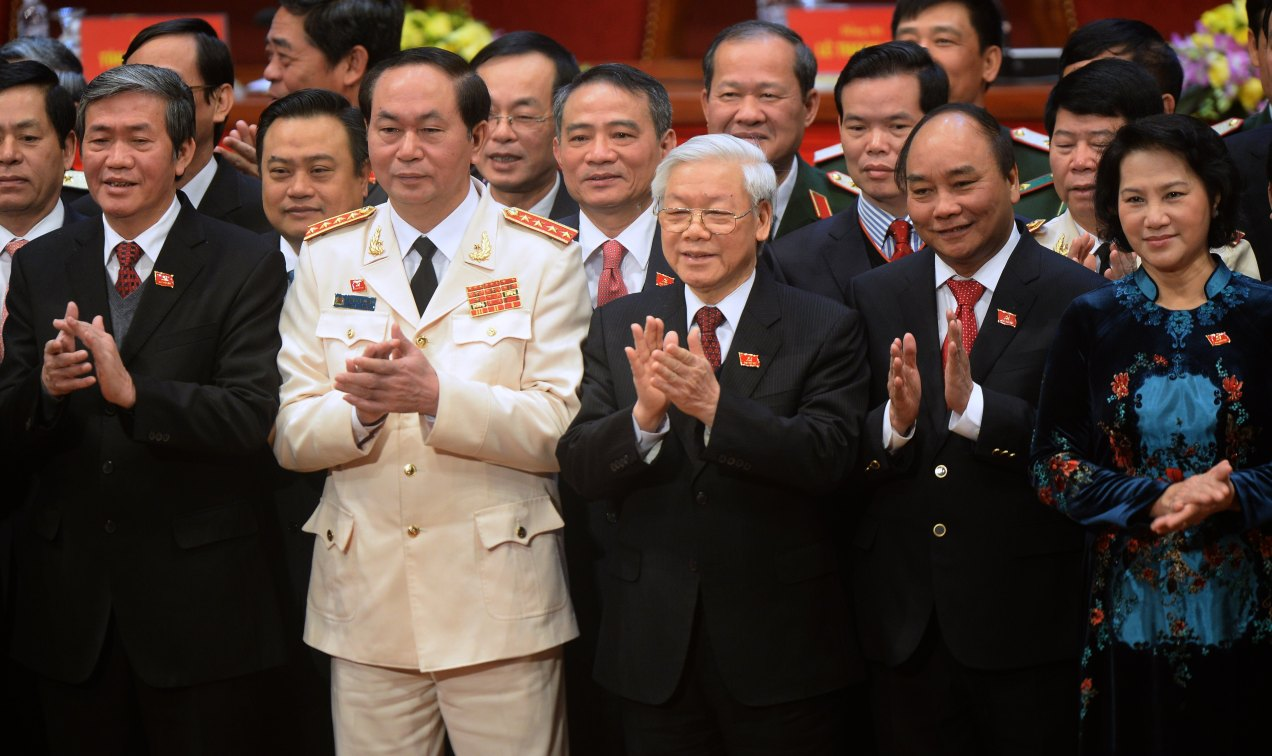 Newly re-elected Vietnam Communist Party Secretary General Nguyen Phu Trong (C) claps with Politburo members Tran Dai Quang (2nd L), Nguyen Xuan Phuc (2nd R), Nguyen Thi Kim Ngan (R) and Dinh The Huynh (L) as they pose with the VCP's new 200-member central committee on the final day of the 12th National Congress of Vietnam's Communist Party (VCP) in Hanoi on January 28, 2016. Vietnam's top communist leader Nguyen Phu Trong was re-elected on January 27 in a victory for the party's old guard which some fear could slow crucial economic reforms in the fast-growing country.AFP PHOTO / POOL / HOANG DINH Nam / AFP PHOTO / POOL / HOANG DINH NAM