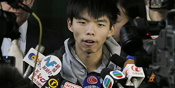 Prominent Hong Kong student protest leader Joshua Wong talks to reporters outside a court in Hong Kong Thursday, Nov. 27, 2014. Wong and other democracy protesters were arrested during a police operation to remove barricades from a protest camp in the unruly Mong Kok district. Wong was given bail and his case adjourned until January 14. (AP Photo/Vincent Yu)