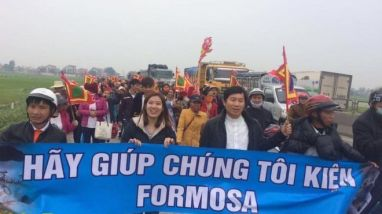 Linh mục Nguyễn Đình Thục (người cầm cờ ngũ sắc) dẫn đoàn tuần hành hôm 14/2. Ảnh: TMCNN
