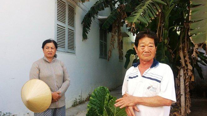 Vợ chồng ông Thương đứng bên dãy nhà mà ông Việt xây lấn để cho thuê. (Hình: Báo Tiền Phong)