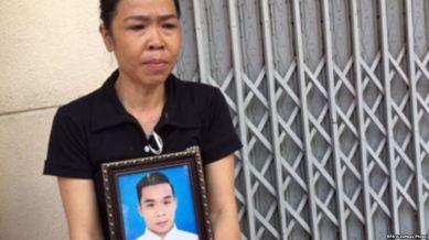 Bà Nguyễn Thị Ái ôm di ảnh con trai, anh Phạm Ngọc Nhung. Ảnh: RFA.