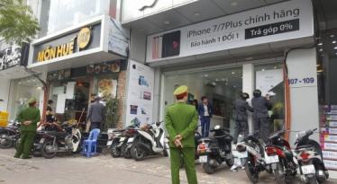 Xe Công an phường Trung Liệt chỉ đạo... bóc những miếng đề-can dán trên cửa kính của các đơn vị kinh doanh. Ảnh: MTG